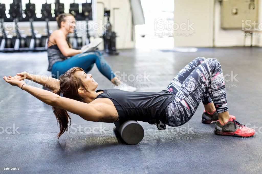 Women exercising on foam rollers in gym stock photo