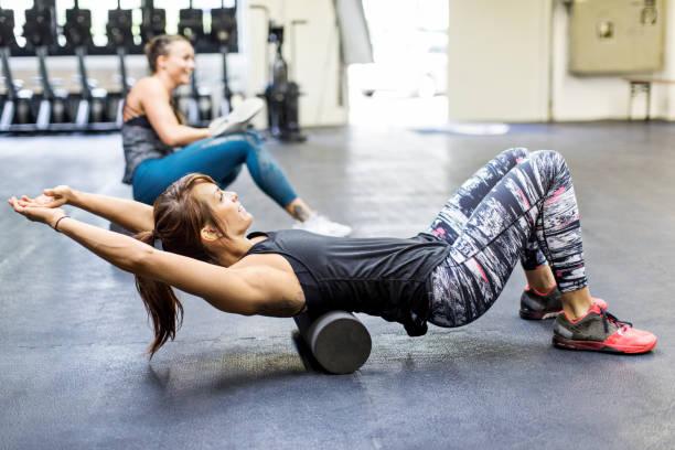 frauen auf schaumstoff rollen im fitness-studio trainieren - alvarez stock-fotos und bilder