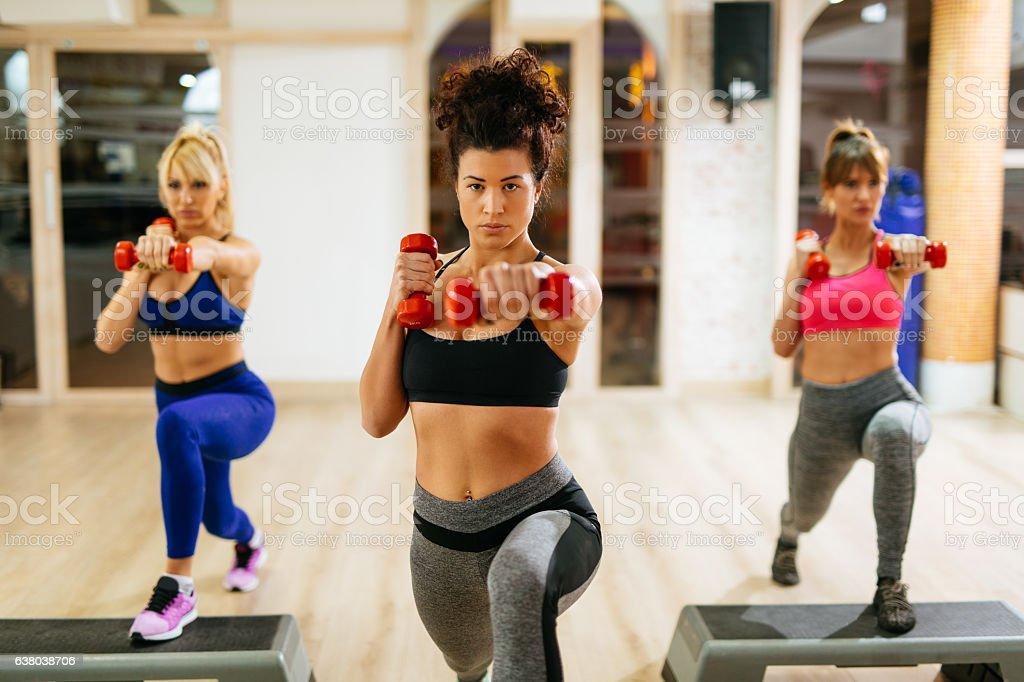 Women exercising step aerobics with dumbbells at the gym. - foto de acervo