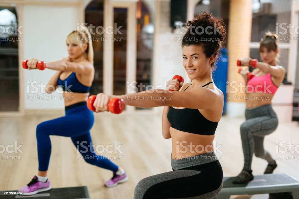 Mulheres exercendo etapa aeróbica com halteres no ginásio. - foto de acervo