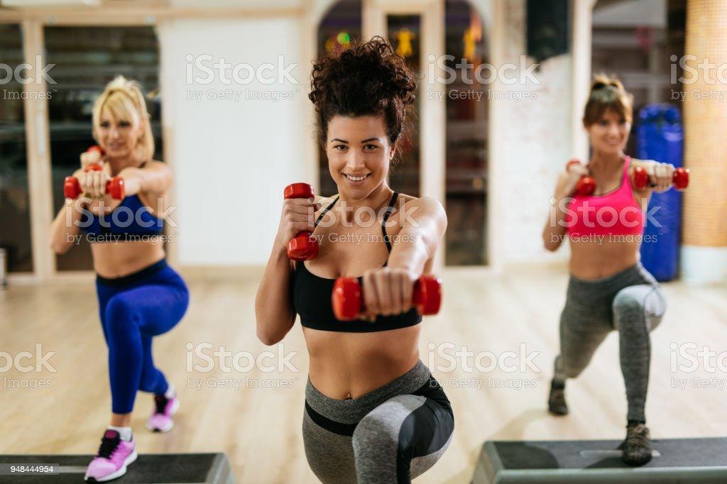 Mulheres exercendo etapa aeróbica com halteres na Academia - foto de acervo
