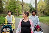 A pregnant fitness instructor is guiding two women around a park as they take a buggy bootcamp class with their children.