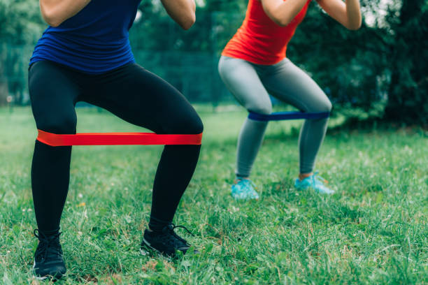 Women Exercising with Elastic Bands in a Park stock photo