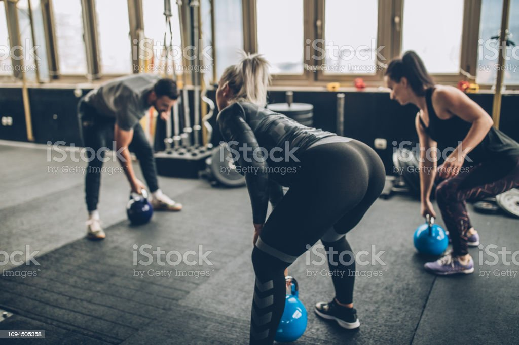 Three people, man fitness trainer and women in gym, instructor on...