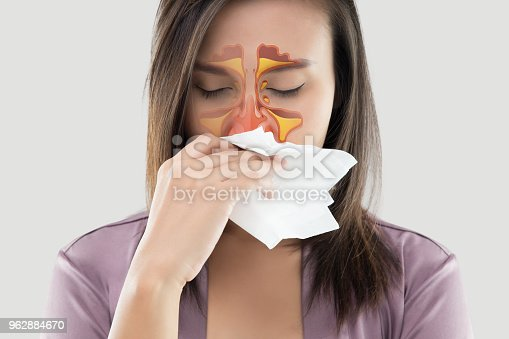 Asian women in satin robes feeling unwell and sinus against gray background. Dust allergies. Flu. People caught cold and allergy.