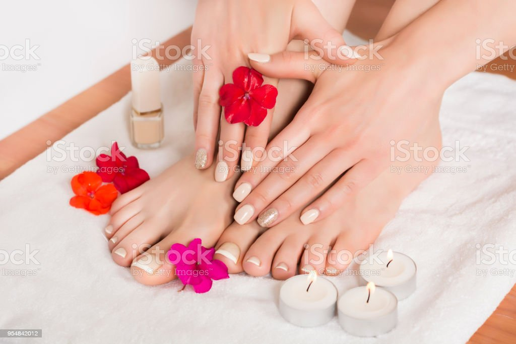 Women feet and hands with french manicured nails and flowers and women feet and hands with french manicured nails and flowers and candles on white towel royalty mightylinksfo
