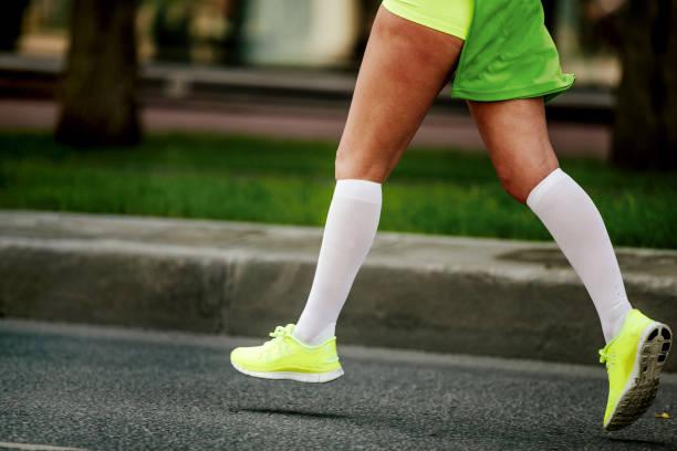 8771ffe19 women feet in white compression socks stock photo