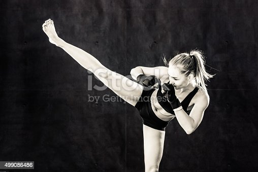 527896028 istock photo Women Fighter Kicking In Black and White 499086486