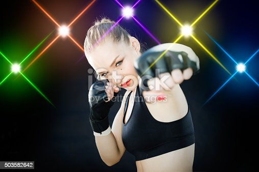 istock Women Fighter Posing With Arena Lighting Flares in the Background 503582642