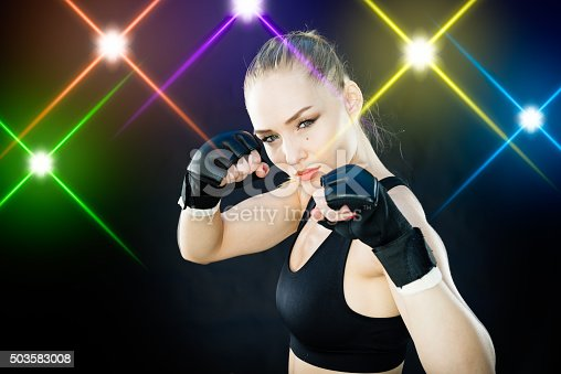istock Women Fighter Posing With Arena Lighting Flares in the Background 503583008