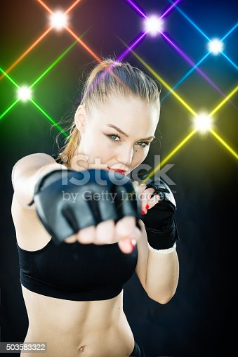 istock Women Fighter Posing With Arena Lighting Flares in the Background 503583322