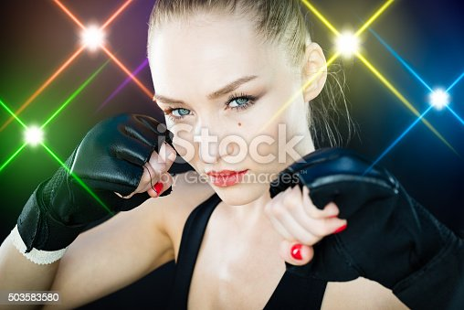 istock Women Fighter Posing With Arena Lighting Flares in the Background 503583580