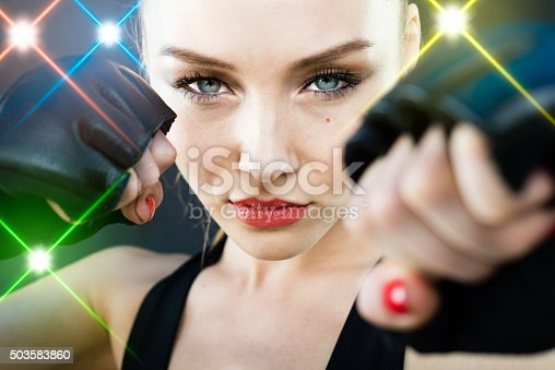istock Women Fighter Posing With Arena Lighting Flares in the Background 503583860