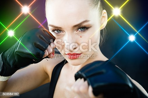 istock Women Fighter Posing With Arena Lighting Flares in the Background 503584182