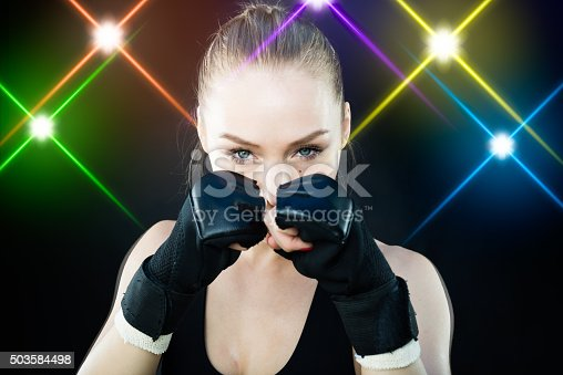 istock Women Fighter Posing With Arena Lighting Flares in the Background 503584498
