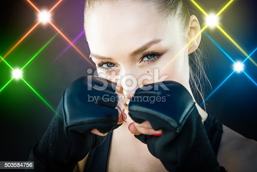 istock Women Fighter Posing With Arena Lighting Flares in the Background 503584756