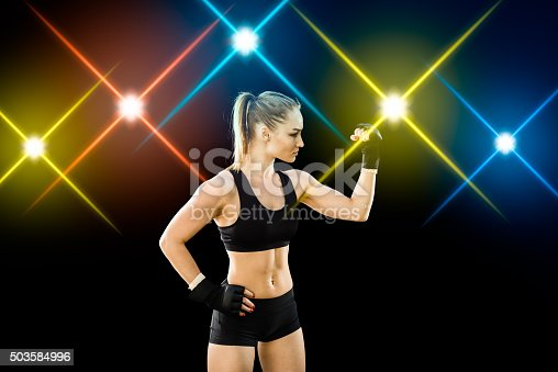 istock Women Fighter Posing With Arena Lighting Flares in the Background 503584996