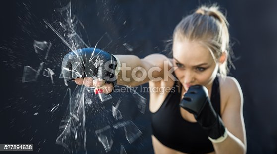 istock Women Fighter Punching Close Up Glass Shattering 527894638