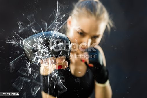 istock Women Fighter Punching Close Up Glass Shattering 527895364