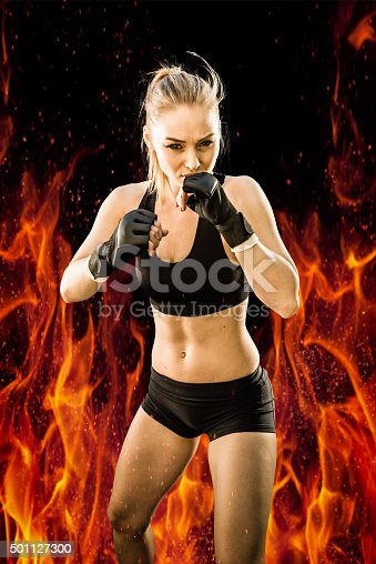 istock Women Fighter Throwing a Punch with a Fire Background 501127300