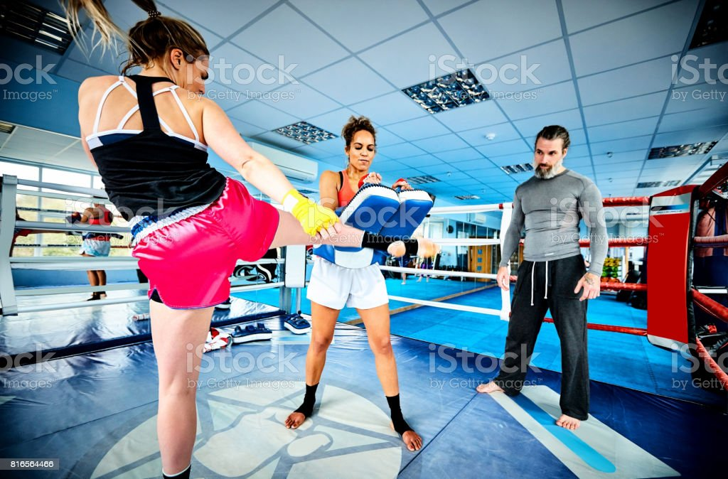 Women fighters practicing kickboxing in gym stock photo