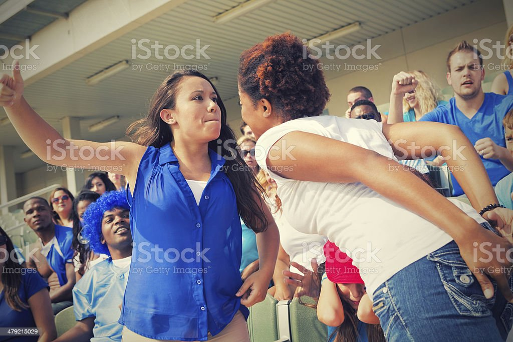Women fighting during sporting event in stadium stock photo