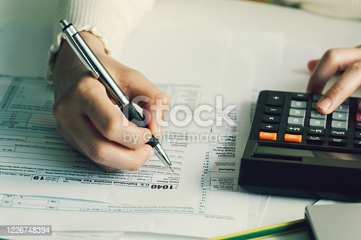Women filling US tax form. tax form us business income office hand fill concept.work from home