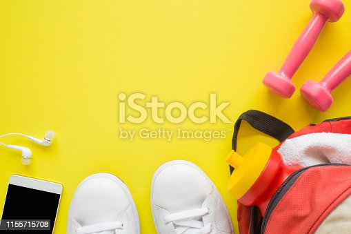 istock Women fitness training accessories. White sport shoes, pink dumbbells, smartphone and bag with water bottle. Empty place for motivational, inspirational text, quote or sayings on yellow background. 1155715708