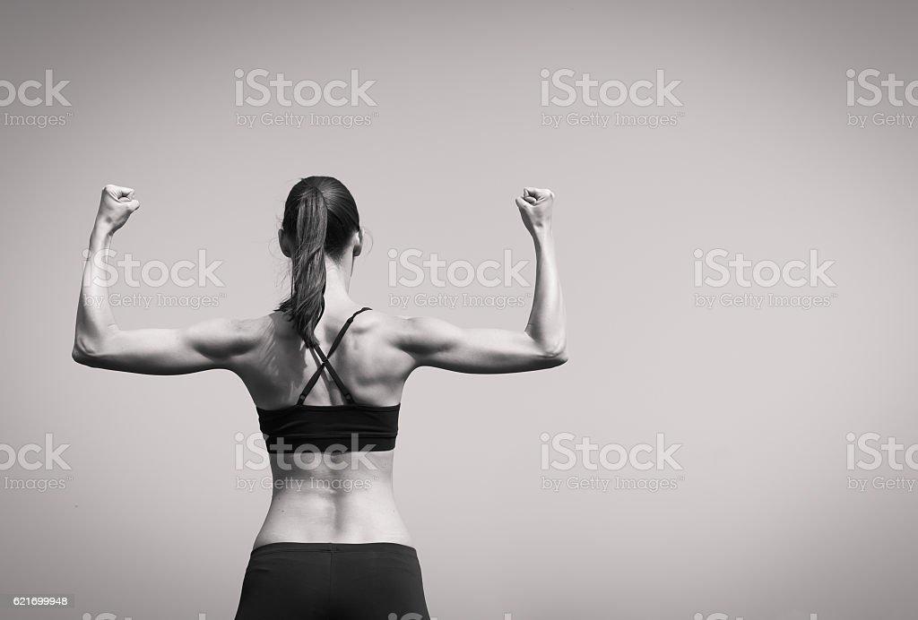 Women flexing her muscles stock photo