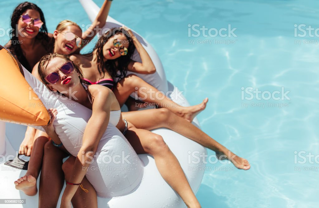Women floating together on a big inflatable toy in pool - Royalty-free Adult Stock Photo