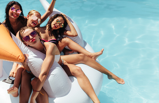 Women Floating Together On A Big Inflatable Toy In Pool Stock Photo - Download Image Now