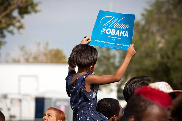 Women for Obama Las Vegas, Nevada - November 1st, 2012: a young African American Girl holds up a sign at a political rally for President Barack Obama atop her Father's shoulders. This was the President's last rally in Nevada before his re-election bid in 2012. barack obama stock pictures, royalty-free photos & images