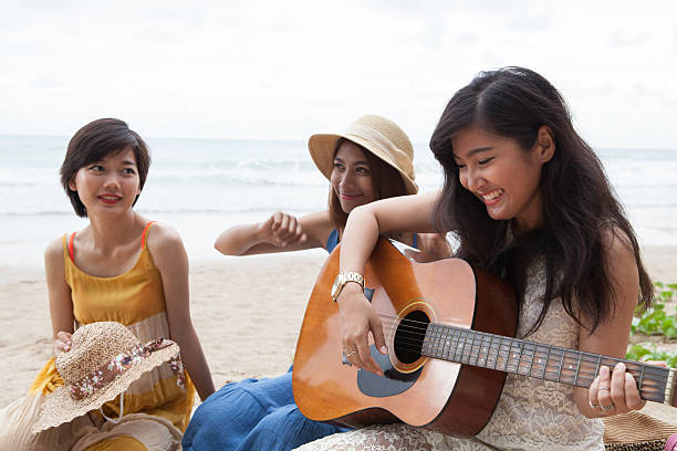 women friend playing guitar in vacation time on destination stock photo
