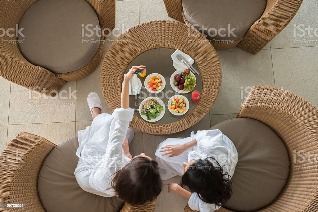 Women Friends at Spa Sharing Healthy Lunch and Taking Selfie stock photo