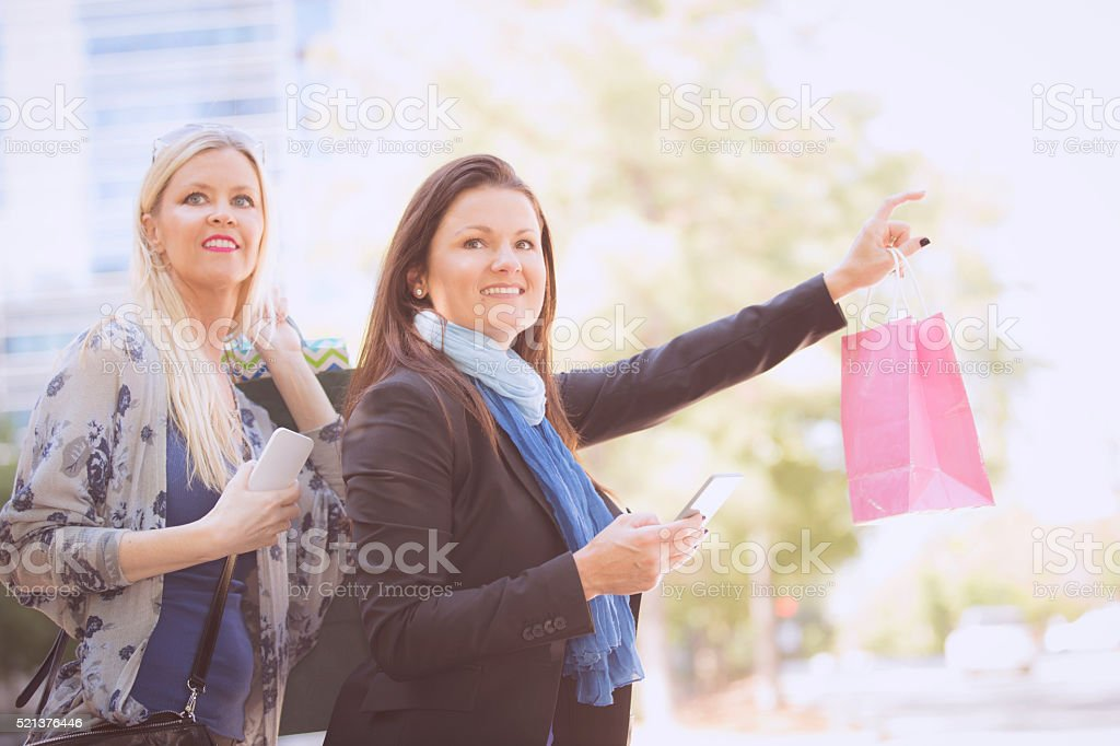 Women friends downtown hailing taxi, City street. Shopping. stock photo