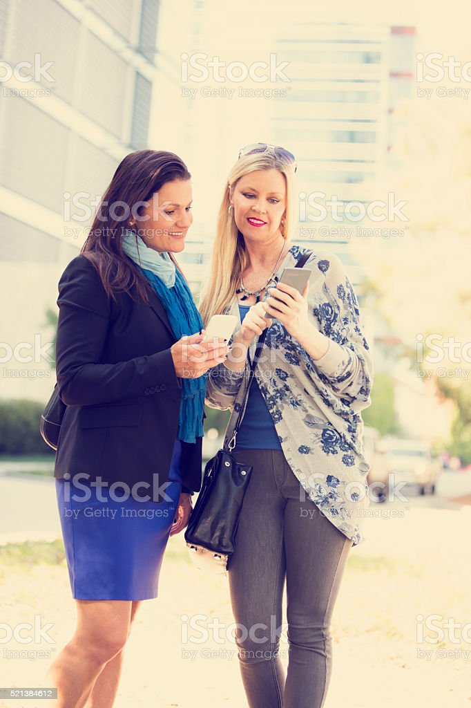 Women friends downtown using cell phones. City street. stock photo