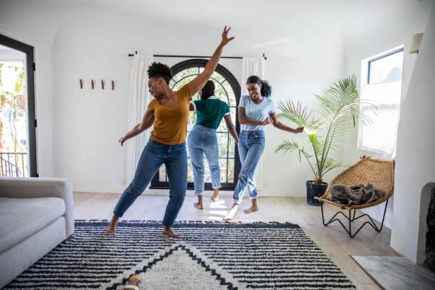 women friends having fun at home dancing and singing in the living room - alegria imagens e fotografias de stock