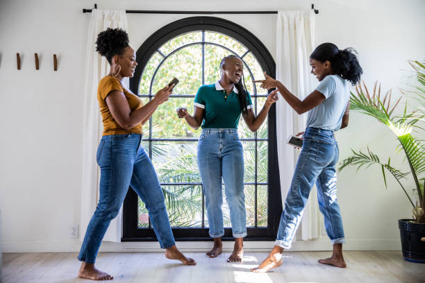 Women friends having fun at home dancing and singing in the living room stock photo