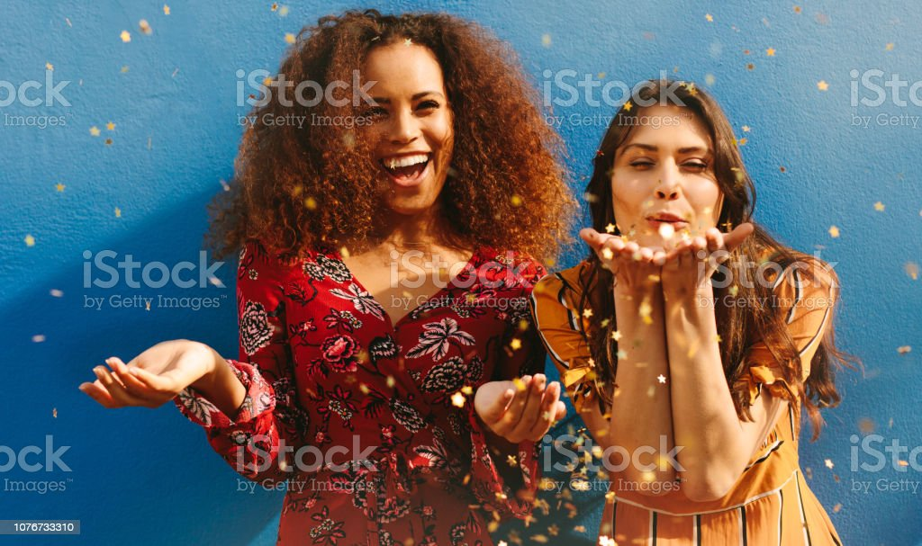Women friends having fun with glitters stock photo