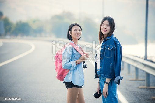 Two Young asian woman traveler with a backpack and travel hat walking on the road. Travel holiday relaxation in Kanchanaburi Thailand