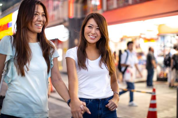 女性の友人で東京の街探索ダウンタウンで買い物して - lgbtqi  ストックフォトと画像