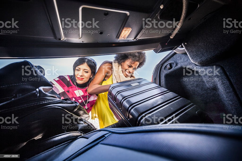 Women friends loading the car to start a great vacation stock photo