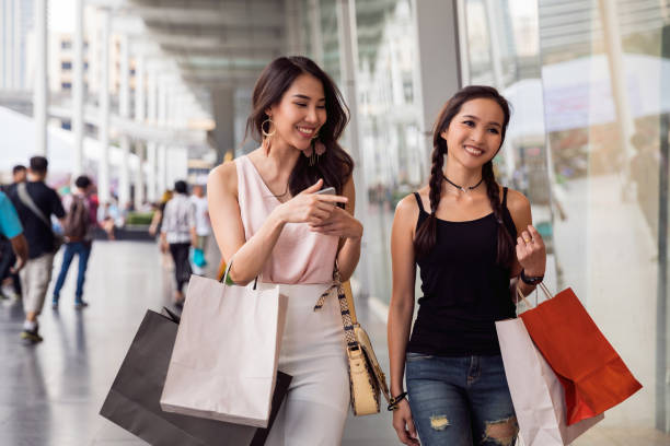Women friends out for shopping in Bangkok city streets Thai friends in Bangkok, excited to spend a Saturday night together thailand mall stock pictures, royalty-free photos & images