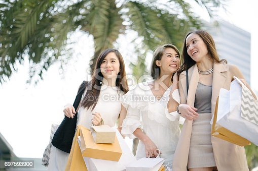 Young beautiful women shopping together, outdoors, smiling
