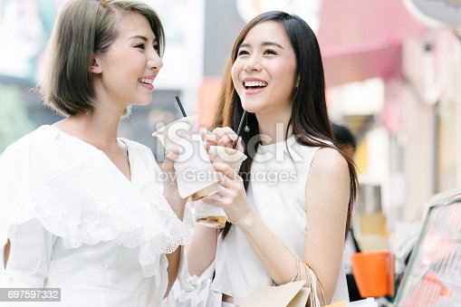 Young beautiful women shopping together, outdoors, smiling, buying refreshing drink