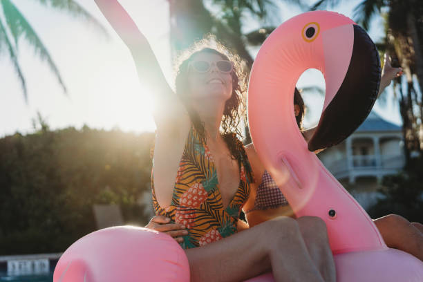 Women friends with flamingo inflatable during swimming pool party - foto stock