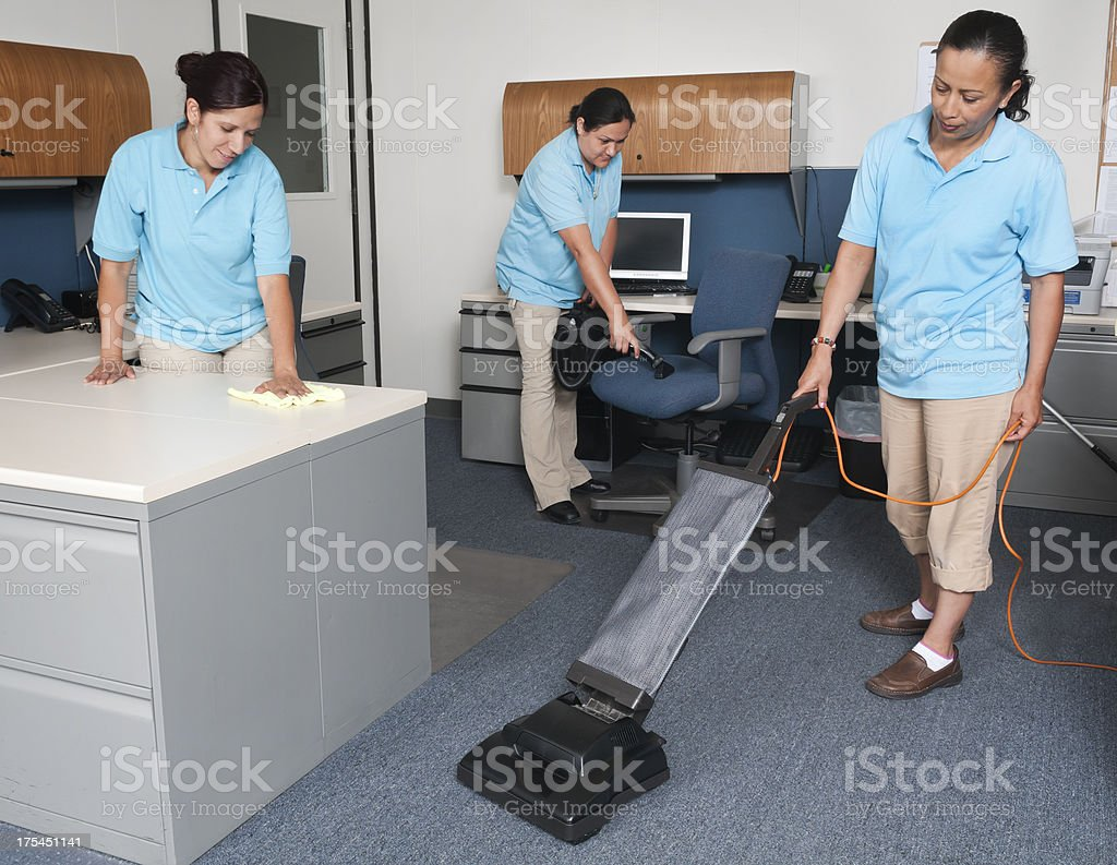 Women from janitorial service cleaning an office stock photo