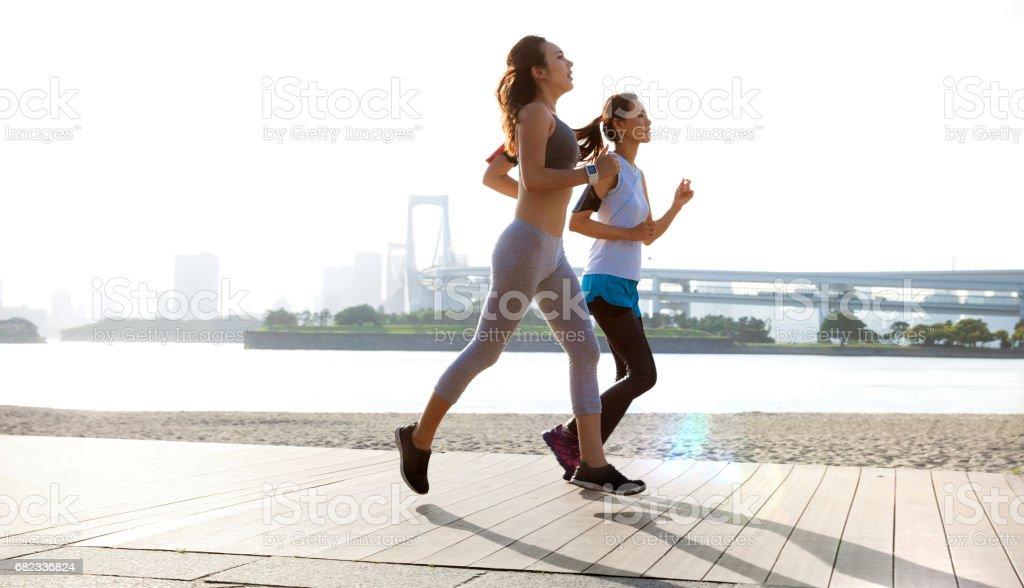 Women getting fit taking run afterwork in Tokyo stock photo