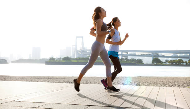 Women getting fit taking run afterwork in Tokyo stock photo