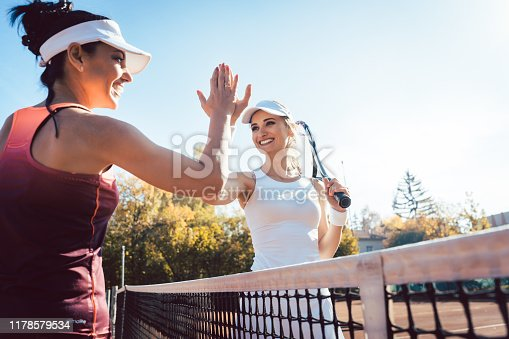Women giving high five after a good and friendly match of tennis